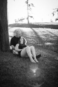 husband and wife cuddling in grass black and white photo- Williston documentary photography